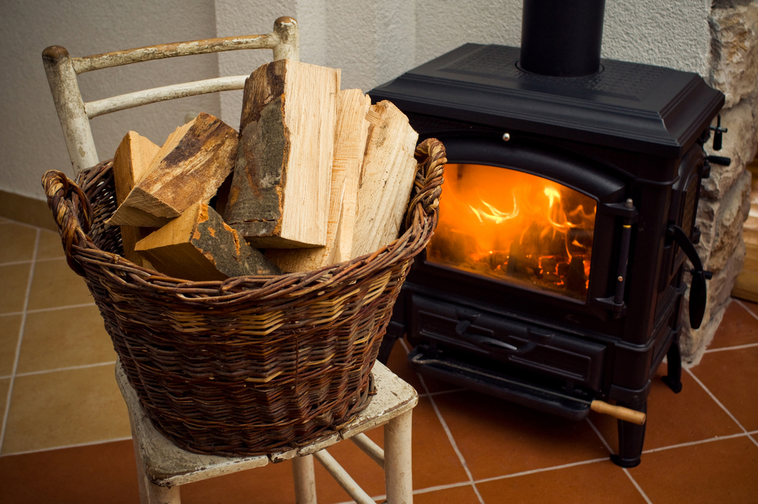 Basket full of logs in front of burning fire